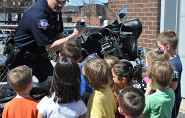 Children viewing a police officer radio and motercycle
